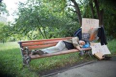 Opinião o ancião desabrigado no banco no parque da cidade Imagens de Stock Royalty Free
