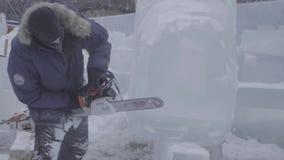 Opinião o escultor que cinzela o gelo movimento Corte o gelo com uma serra de cadeia Corte e faça a escultura de gelo Desbastando vídeos de arquivo