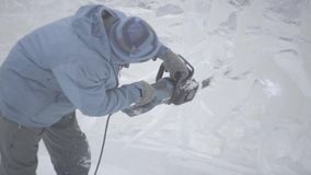Opinião o escultor que cinzela o gelo movimento Corte o gelo com uma serra de cadeia Corte e faça a escultura de gelo Desbastando filme