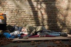 Opinião o homem desabrigado que dorme no cartão na terra imagem de stock