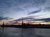 Opinião o Peter e o Paul Fortress através do rio no crepúsculo nos raios do sol de ajuste imagem de stock