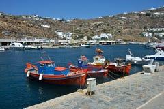 A opinião o porto de Mykonos com construções brancas e o pescador coloriu barcos típicos amarrados imagens de stock royalty free