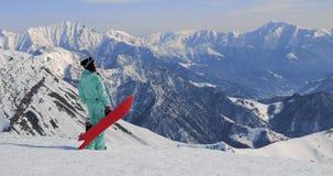 Opinião o snowboarder fêmea com o snowboard em umas mão e montanha da apreciação filme