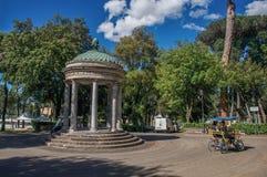 Opinião o templo e ciclistas pequenos na casa de campo Borghese em Roma Imagem de Stock Royalty Free
