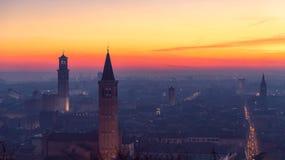 Opinião panorâmico bonita do por do sol da cidade velha torre de sino de Verona, de Torre Lamberti e de Santa Anastasia coberta c imagens de stock royalty free