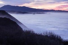Opinião panorâmico da paisagem depois que por do sol no litoral atlântico no céu cor-de-rosa com ondas enormes, país basque, fran fotografia de stock