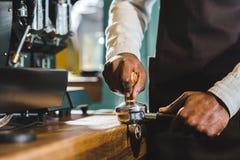 opinião parcial do close-up do barista no avental que prepara o café imagem de stock royalty free