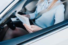 opinião parcial a mulher de negócios com o jornal no assento de motoristas imagem de stock royalty free