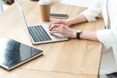 opinião parcial a mulher de negócios que datilografa no portátil no local de trabalho com café para ir e registrar foto de stock royalty free