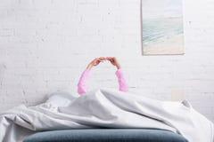 opinião parcial a mulher nos pijamas usando o smartphone ao descansar na cama foto de stock royalty free