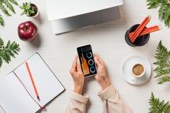 opinião parcial o freelancer fêmea que usa o smartphone com gráficos e cartas na tela na tabela com o livro de texto do café do p fotografia de stock royalty free