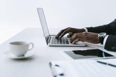 opinião parcial o homem de negócios afro-americano que datilografa no portátil no local de trabalho foto de stock royalty free