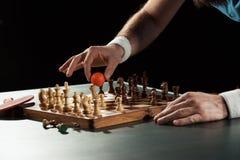 opinião parcial o jogador de tênis que põe a bola de tênis sobre a placa de xadrez com figuras Foto de Stock