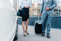 opinião parcial os executivos com bagagem que andam ao carro imagem de stock