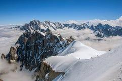 Opinião picos nevado e alpinistas de Aiguille du Midi em cumes franceses Foto de Stock Royalty Free