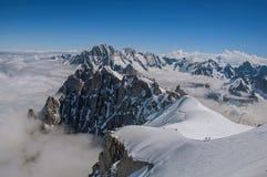Opinião picos nevado e alpinistas de Aiguille du Midi em cumes franceses Fotografia de Stock