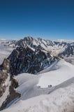 Opinião picos nevado e alpinistas de Aiguille du Midi em cumes franceses Foto de Stock
