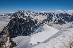 Opinião picos nevado e alpinistas de Aiguille du Midi em cumes franceses Imagens de Stock