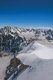 Opinião picos nevado e alpinistas de Aiguille du Midi em cumes franceses Fotos de Stock Royalty Free