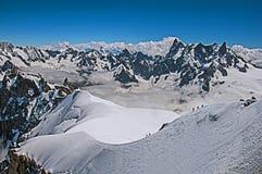 Opinião picos nevado e alpinistas de Aiguille du Midi em cumes franceses Fotos de Stock