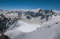Opinião picos nevado e alpinistas de Aiguille du Midi em cumes franceses Imagens de Stock Royalty Free