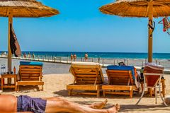 Opinião a praia e os veraneantes nos vadios nas costas da queimadura do Mar Vermelho no sol em férias imagem de stock royalty free