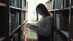 Opinião que traseira da silhueta uma jovem mulher bonita anda entre as estantes na biblioteca Conceito: educacional video estoque