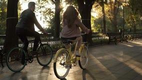 Opinião rara os pares ou os amigos novos caucasianos que montam suas bicicletas no parque ou no bulevar vazio da cidade no verão filme