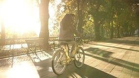 Opinião rara um par feliz novo ou os amigos que montam suas bicicletas no parque ou no bulevar vazio da cidade no verão vídeos de arquivo