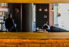 Opinião refletida uma loja e clientes do café em um espelho em uma parede de tijolo Fotos de Stock Royalty Free
