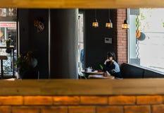Opinião refletida uma loja e clientes do café em um espelho em uma parede de tijolo Fotos de Stock