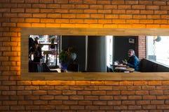 Opinião refletida uma loja e clientes do café em um espelho em uma parede de tijolo Imagem de Stock Royalty Free