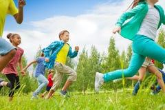 Opinião running das crianças no campo verde Foto de Stock Royalty Free