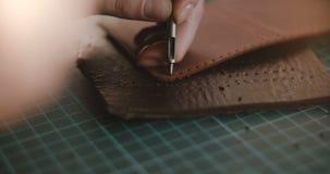 Opinião super do close-up disparada das mãos fêmeas profissionais que fazem furos na parte de couro pequena com martelo e perfura filme