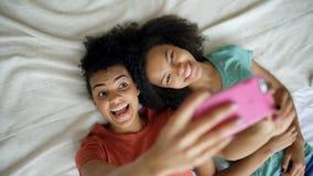 Opinião superior as amigas engraçadas bonitas da raça misturada que fazem o retrato do selfie na cama no quarto em casa foto de stock royalty free