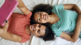 Opinião superior as amigas engraçadas bonitas da raça misturada que fazem o retrato do selfie na cama no quarto em casa fotos de stock