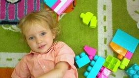Opinião superior a criança bonito que joga com multi desenvolvimento infantil colorido dos blocos de apartamentos no infantário video estoque