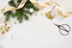 Opinião superior da decoração do Natal do modelo e fita do ouro, flatlay em um fundo de madeira branco, com lugar para seu texto fotos de stock