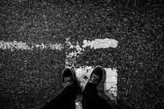 Opinião superior da ?a pessoa preto e branco suja em uma estrada Fotos de Stock