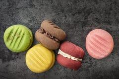 Opinião superior das cookies coloridas na ardósia Foto de Stock