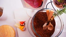 Opinião superior de feijões de café no fundo branco limpo com composição de copos de café, pássaros coloridos, lâmpadas, jardim n Imagem de Stock Royalty Free
