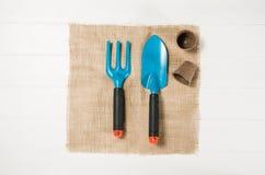 Opinião superior de ferramentas de jardinagem no fundo de madeira branco das pranchas Fotos de Stock