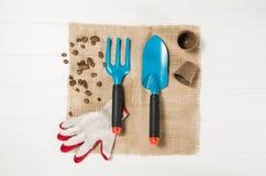 Opinião superior de ferramentas de jardinagem no fundo de madeira branco das pranchas Fotos de Stock Royalty Free