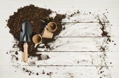 Opinião superior de ferramentas de jardinagem no fundo de madeira branco das pranchas Imagem de Stock