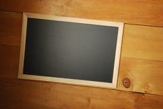 Opinião superior de placa de giz com fundo de madeira fotografia de stock