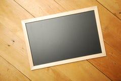 Opinião superior de placa de giz com fundo de madeira imagem de stock