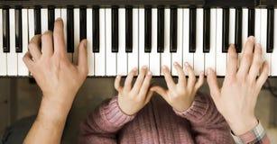 Opinião superior de teclado de piano e mãos da mãe e do pai da criança Fotografia de Stock