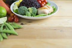 A opinião superior do alimento limpo na tabela de madeira no disco tem o vegetal e a galinha Fotos de Stock