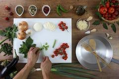 Opinião superior do alimento, mãos que cortam o aipo na placa de desbastamento branca no trabalho superior de madeira da cozinha Fotografia de Stock Royalty Free