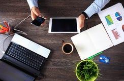 Opinião superior do desktop de madeira do moderno do vintage, mãos masculinas usando o portátil Imagem de Stock